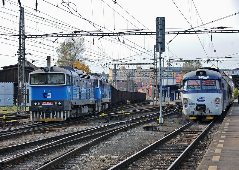 A freight headed by CD Cargo 753-754 and 753-755 runs into the yard at Kralupy nad Vitavou on 22 October 2010 passing 451-098 which is forming a local passenger service to Praha