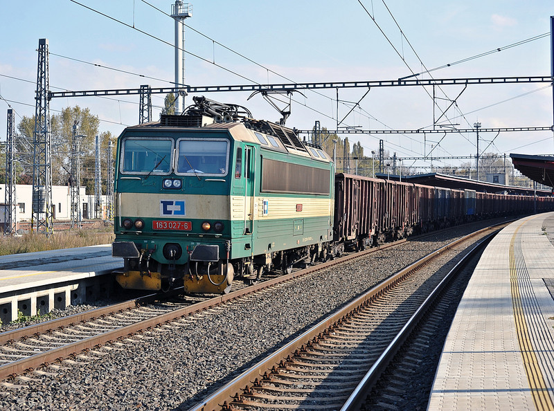 CD Cargo 163-027 runs through the main line platforms at Kolin with a freight heading toward Praha on 23 October 2010