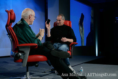 Jobs holds up the iPhone during his interview with Mossberg at D5 in 2007.