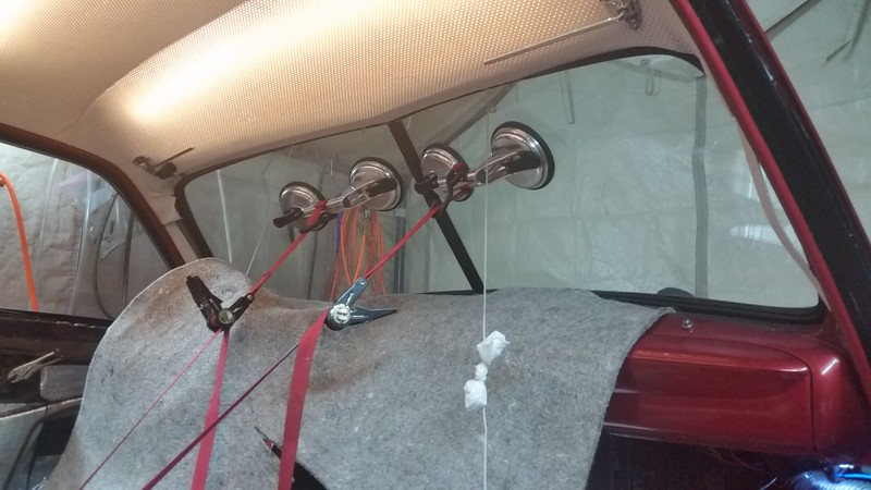 """If you are installing your windshield by yourself, with no help, here is how you do it ! ! !  You can get these glass suction cups for seven bucks each on Amazon, or Harbor freight. Then tie the suction cups back to a solid support in the floor. I used one of the bolts for the seatbelts. Those red strips are so tight you could play a tune on them. Seriously. The padding is taped to the top of the dash so """"just in case"""" one of the suction cups comes loose, it won't ruin the dash or steering wheel. The pull string/rope is hanging from the area where it starts gettin' reallll tough to make the inner lip flip over the ledge of the frame. You can see that the inner lip on the bottom and outer edges and half way across each window panel is in place, but not in the middle of the top."""