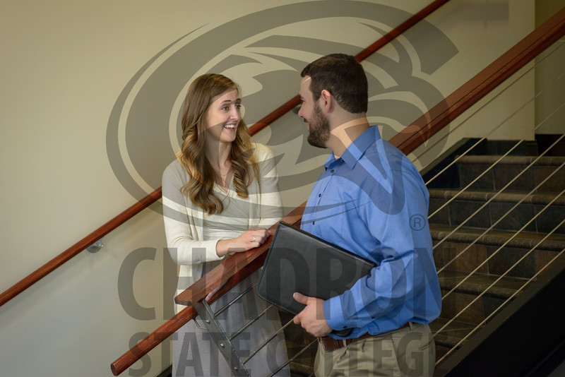 Kate Pope and Austin Stephens speak to each other at the office. (Photo by Daniel Binkard/Chadron State College)