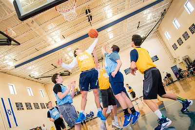 Teens practice team building and athleticism while playing basketball in a gymnasium in Baltimore, Maryland.