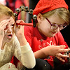 Kevin Harvison | Staff photo<br /> Pictured form left, Keagan Glenna peers past the bright lights of S. Arch Thompson Auditorium Monday as Jaylynn Hall, right, makes sure the bells on her tambourine is ready before the start of A Holiday of Music Christmas Program.