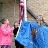 Kevin Harvison | Staff photo<br /> Pictured from left, fourth grade students, Ava Zietz, Haiden Hice and Cheyenne Whorton proudly raise the State and Nation Flags before the start of school at Emerson Elementary School.
