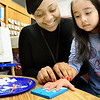 Kevin Harvison | Staff photo<br /> Washington Early Childhood Center/Kibois Headstart student Lynn Morales, right, gets some help working on a Christmas ornimante with Kay Banks.