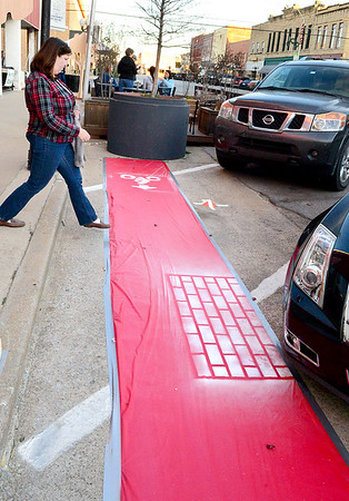 Kevin Harvison | Staff photo<br /> A pedestrian steps off the Choctaw Avenue curb on to a red vynle display showing where the future brick bike trail is planned during the block party Thursday.
