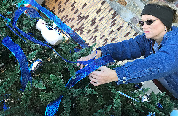 KEVIN HARVISON | Staff photo <br /> Shannon Webster puts the finishing touches on a downtown Christmas Tree .
