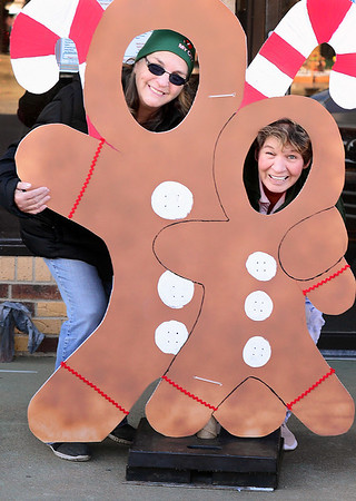"KEVIN HARVISON | Staff photo<br /> Pictured from left, Connie Baucom and DeLona Jones try out the Ginger Bread cut out ""photo op"" that will be on display on Choctaw Avenue for spectators of the Christmas Parade to take advantage of Thursday."