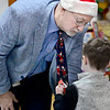 KEVIN HARVISON | Staff photo<br /> Suspense is in the air while McAlester Public Schools Superintendent Randy Hughes left, looks on as William Gay Kindergarden student Bostyn Tate, right, unwraps the Elf In The House book that Hughes will read to the class.