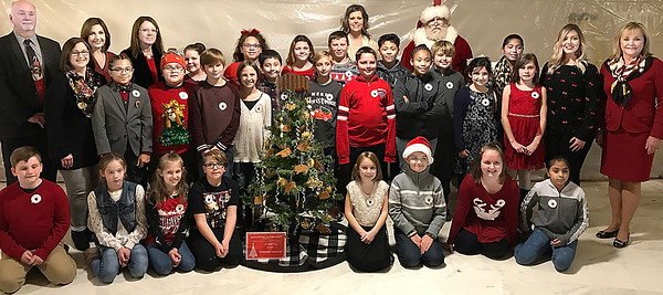 KEVIN HARVISON | Staff photo <br /> Several pose around the Christmas Tree decorated by Emerson Elementary Students. The tree will be on display inside the State Capitol building.