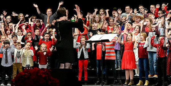 KEVIN HARVISON | Staff photo<br /> Edmond Doyle Elementary School performed Rock the Hall Christmas Program directed by Christina Braswell, center, at S. Arch Auditorium.