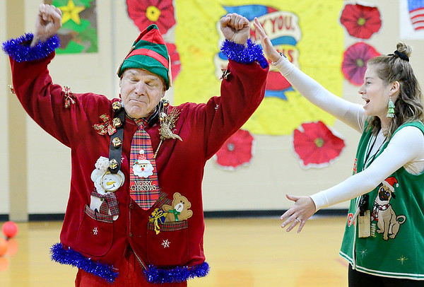 KEVIN HARVISON | Staff photo<br /> Pictured left, Parker Intermediate Center teacher Brent Grilliot is announced the winner of the PIC Best Dressed Christmas Cheer contest among the campus teachers as art teacher Rebecca Ruiz, right helps hype the crowd of students.