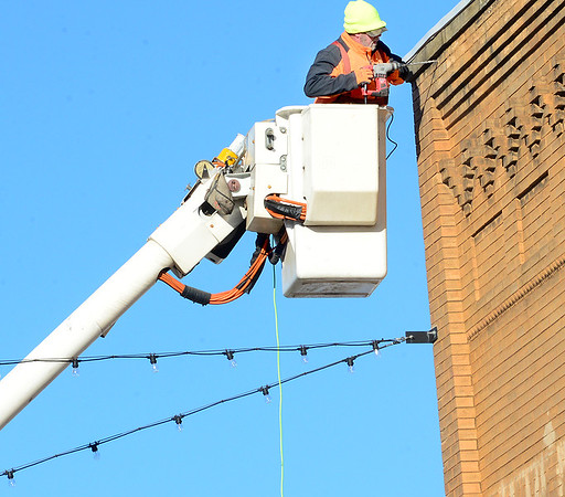 KEVIN HARVISON | Staff photo<br /> McAlester City worker attempts to drill a hole in a downtown building for a bracket to hang more Christmas decorations.