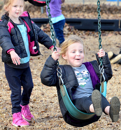 KEVIN HARVISON | Staff photo<br /> Jefferson Early Childhood Center students Savanna Burse, left and Timberleigh Clayton, right, enjoy the mild weather at recess.