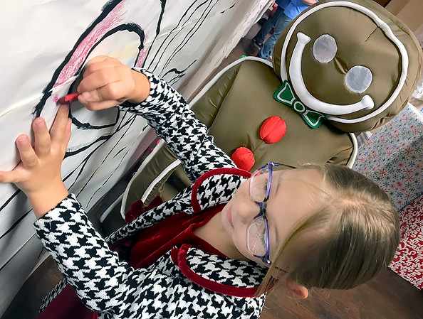 KEVIN HARVISON | Staff photo<br /> Caris Hamilton colors a giant candy cane wall decoration while a costume Ginger Bread Man watches during the King's House Christmas free experience for kids and families.
