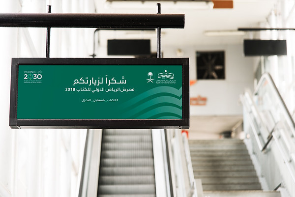 Hanging sign mockup in front of an escalator