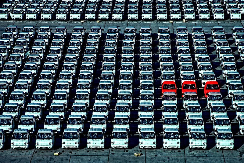 All new cars just off a ship in the Port of Mazatlan, Mexico. Why is it all white and only three red ones?