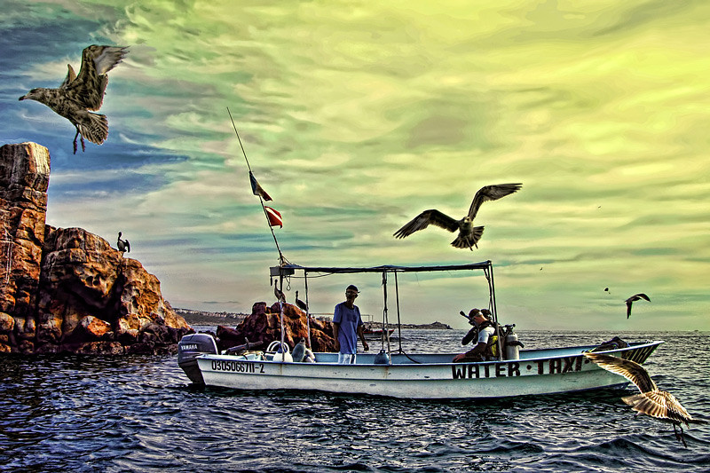 """A water taxi slowing down to anchor near """"land's end"""" for deep sea diving. photographed at Cabo San Lucas, Mexico."""