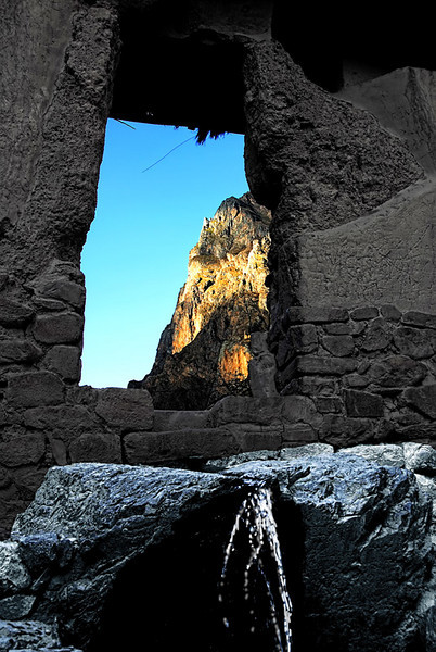 A nutural spring (foreground) is well protected with stone walls and reed roof at top. This shot was taken at Ollantaytambo, Peru.