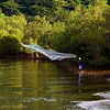 A fisherman hurls his net at the river bank in Calayo.