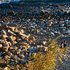 A woman making her earlu morning stroll along the rocky shore of Lake Nahuel Huapi, Bariloche, Argentina.