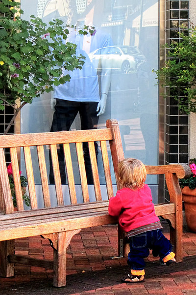 A young shopper admiring a man's attire with the help of a wooden bench. Spotted in broadway Plaza Mall, Walnut Creek, California.