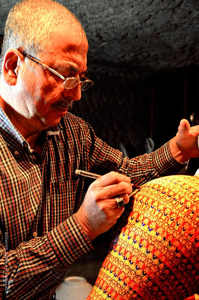 A pottery artist painting a ceramic jar in Cappadocia, Turkey.