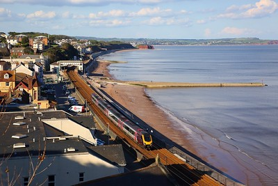 220007 running on opposite line works the 1V57 1305 Manchester Piccadilly at Dawlish on the 11th May 2019