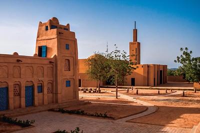 01 Dandaji, Niger. 2016 gebaute neue Moschee (Hintergrund) und in eine öffentliche Bibliothek umgebaute ehemalige Moschee (im Vordergrund)