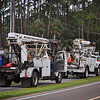 Utility crews waiting for the lighthouse and other buildings to get near, so they can lower the lines.