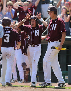 Newman's Josh Fitzegerald (#9) celebrates after Peyton Scott (#3) scored during the fifth inning in the Class 1A State Championship at Principal Park in Des Moines, Iowa on Saturday, August 1, 2015. (Photo by Dylan Heuer/Iowa Cubs)