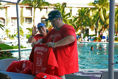 Jodi and Charley distributing team uniforms by the pool