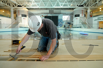Bob Campbell, a tile setter with Paragon Tile & Stone, lays down grates for the wave pool at the Evergreen Wings and Waves Waterpark in McMinnville on Friday.