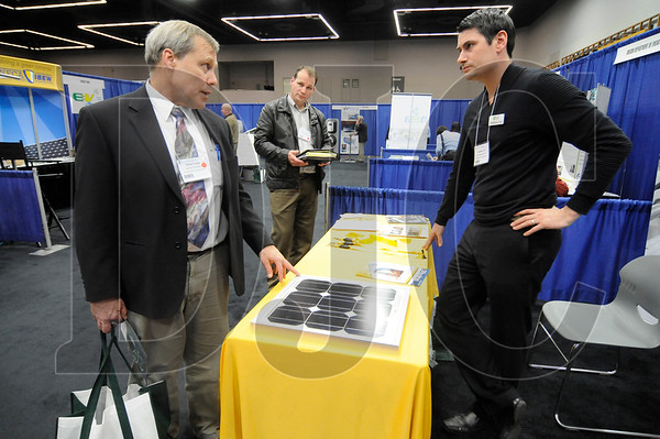 Steve Clapp, left, of Emerick Construction, and Mike Dutton, center, of IBEW Local 48, speak about solar energy with Matthew Lind of Advanced Energy Systems.