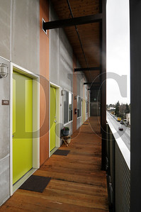 Residences at the recently completed ecoFLATS aparment building open to the outdoors, a design intended to cut energy used to light, cool, and heat interior corridors.  Sam Tenney/DJC
