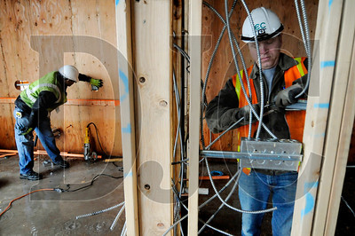 John Knapp, left, and Yllar Helmik, both members of IBEW Local 48 and journeyman electricians with minority-owned Ampere Electric, work at the site of the Killingsworth Station building in Portland on Friday.