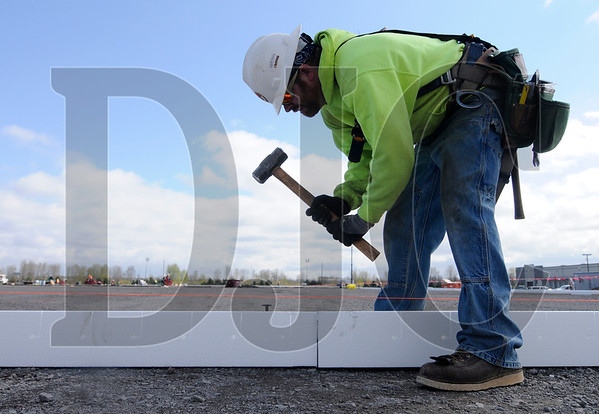 Journeyman carpenter Christian Thompson, an employee of Howard S. Wright, sets slab edge form at the site of an industrial building project near the Port of Portland on Thursday.  Sam Tenney/DJC