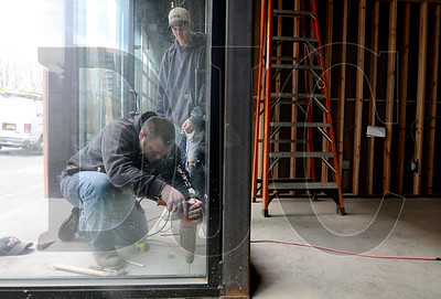 Superintendent Steve Myers, left, and carpenter Jason Bogers install a door stop on the site of a Northwest Flanders Street renovation on Tuesday.  Five units have been built within the 20,000 square foot structure, which formerly housed Ford Graphics.