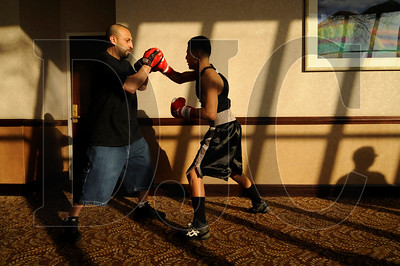 James Ramos, left, a coach and trainer with Capitol Boxing Club in Salem, warms up boxer Jose Delgado in a hotel hallway prior to the start of the bouts.