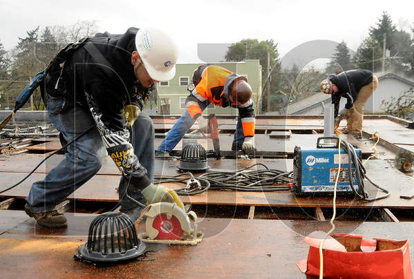 Michael Aguilar, left, a carpenter with Colas Construction, Inc., and iron workers Chad Wallace, center, and Lonny Beede, of A36 Structures, work to install support posts for solar panels on the roof of the June Key Delta Community Center in Northeast Portland on March 25.  Sam Tenney / DJC Staff