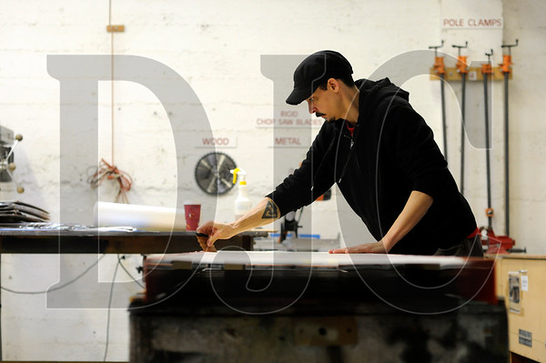 Sign Wizards production manager Clint Nickelson works on a sign in the company's Southeast Portland shop on Monday.