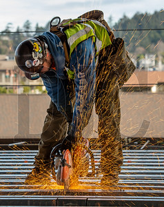 Levi Peckham, a journeyman ironworker with Local 86 out of Seattle and an employee of Corona Steel, cuts a section of steel pan decking on the second story of the building. (Josh Kulla/DJC)