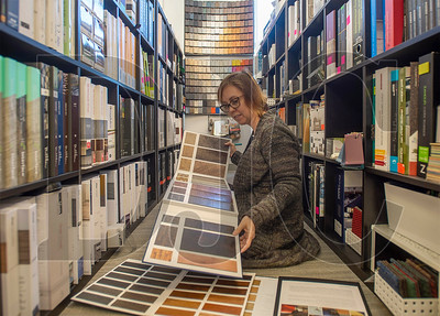 Lisa Sneddon, an interior designer with LRS Architects, pores through a book of flooring samples at krowdsourced, a Portland materials library catering to the building industry. (Josh Kulla/DJC)