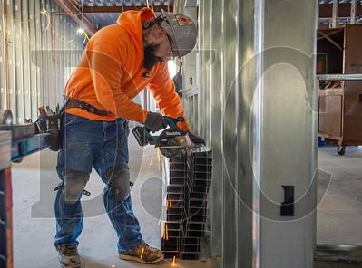 Journeyman EIS carpenter Max Hansen, a member of Local 146 and an employee of Cascade Acoustics, cuts a section of steel stud. (Josh Kulla/DJC)