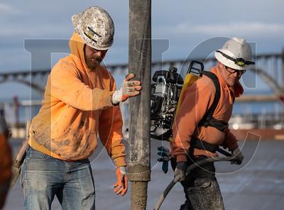 Journeyman laborers Jake Bateman, left, a member of Local 737 and an employee of Industrial Concrete, and Robert Reed, also a member of Local 737 and an employee of T Gerding Construction, pour a roof slab. (Josh Kulla/DJC)