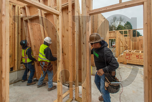 Eddie Lorenzo, right, a carpenter with Jose Luis Morales Construction, guides colleagues as they install a wall panel. (Josh Kulla/DJC)