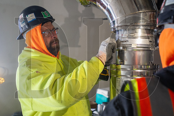 Journeyman sheet metal technician Jeremy Moore, a member of Local 16 and an employee of Alliant Systems, connects two sections of flue for the building boiler. (Josh Kulla/DJC)