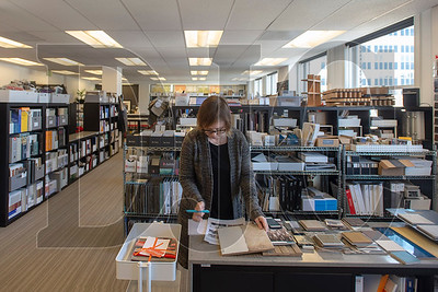 Lisa Sneddon, an interior designer with LRS Architects, examines flooring samples at the krowdsourced materials library in downtown Portland. (Josh Kulla/DJC)
