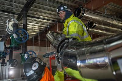Apprentice sheet metal technician Jeremy Annett, a member of Local 16 and an employee of Alliant Systems, installs a section of boiler flue. (Josh Kulla/DJC)