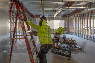 Apprentice HVAC technicians Tom Glore (left) and John Felix, both members of Local 16 and employees of Alliant Systems,  work inside a classroom. (Josh Kulla/DJC)